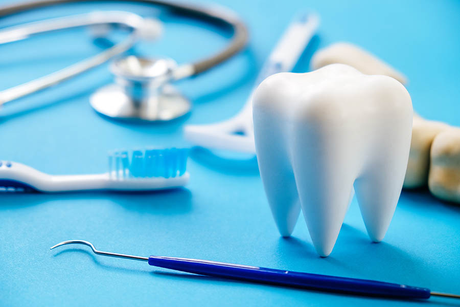Dental Model And Dental Equipment On Blue Background, Concept Im